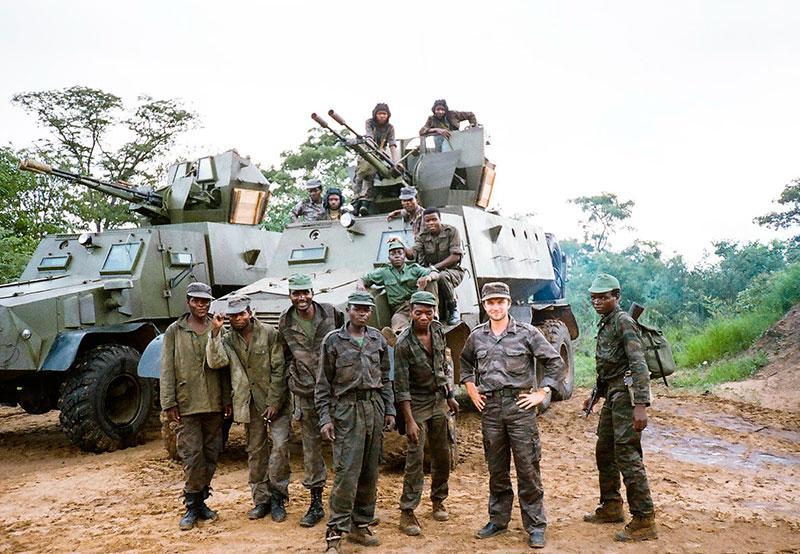 Военный учебный центр под г. Менонге. Переводчик капитан Павел Акимов (второй справа) с группой бойцов ФАПЛА у специальных боевых машин сопровождения колонн. 1990 год. Фото В. Сагачко.