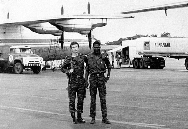 Военный переводчик старший лейтенант И. Сечин с бойцом охраны аэродрома в Намибе. На заднем плане: советский транспортный самолет Ан-12 авиаотряда ГВС в Анголе заправляется топливом от национальной компании «Sonangol». 1985 год. Фото И. Сечина.